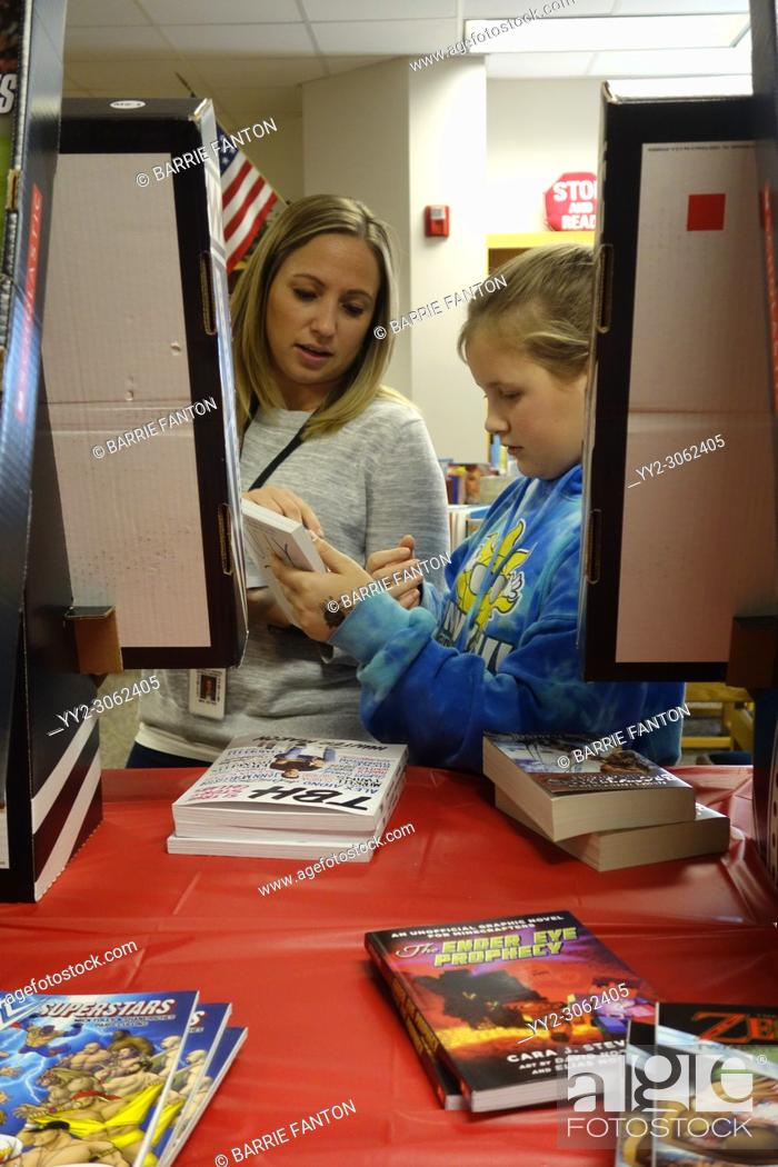 Stock Photo: 6th Grade Girl and Teacher Conferring in School Library, Wellsville, New York, USA.