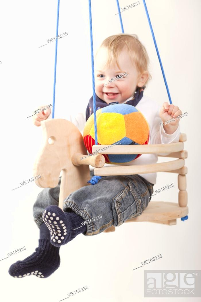 Stock Photo: toddler boy in swing whit background isolated.