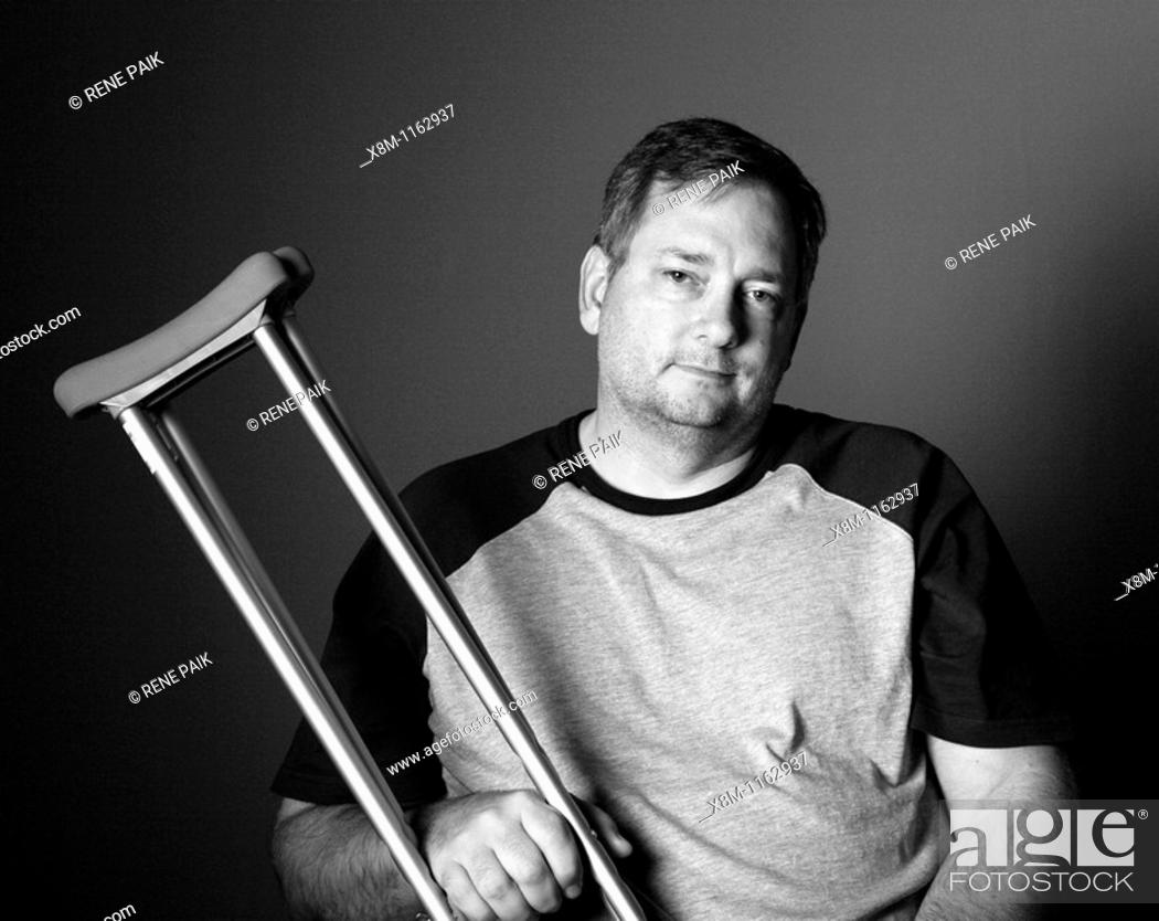 Stock Photo: After surgery, a man with a surgically repaired broken leg with crutches.