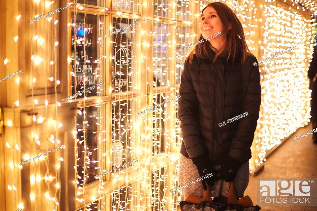 Stock Photo: Woman by curtain of fairy lights smiling, Odessa, Odessa Oblast, Ukraine, Europe.