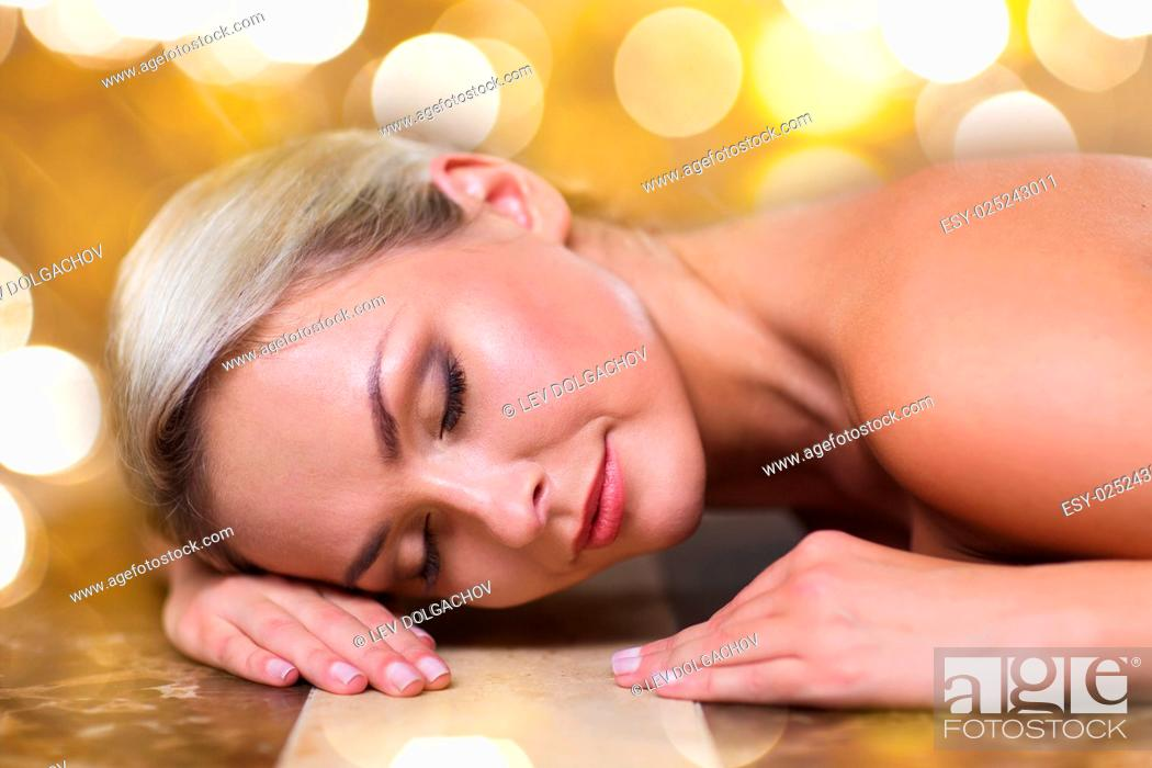 Stock Photo: people, beauty, spa, healthy lifestyle and relaxation concept - beautiful young woman lying on hammam table in turkish bath over holidays lights background.