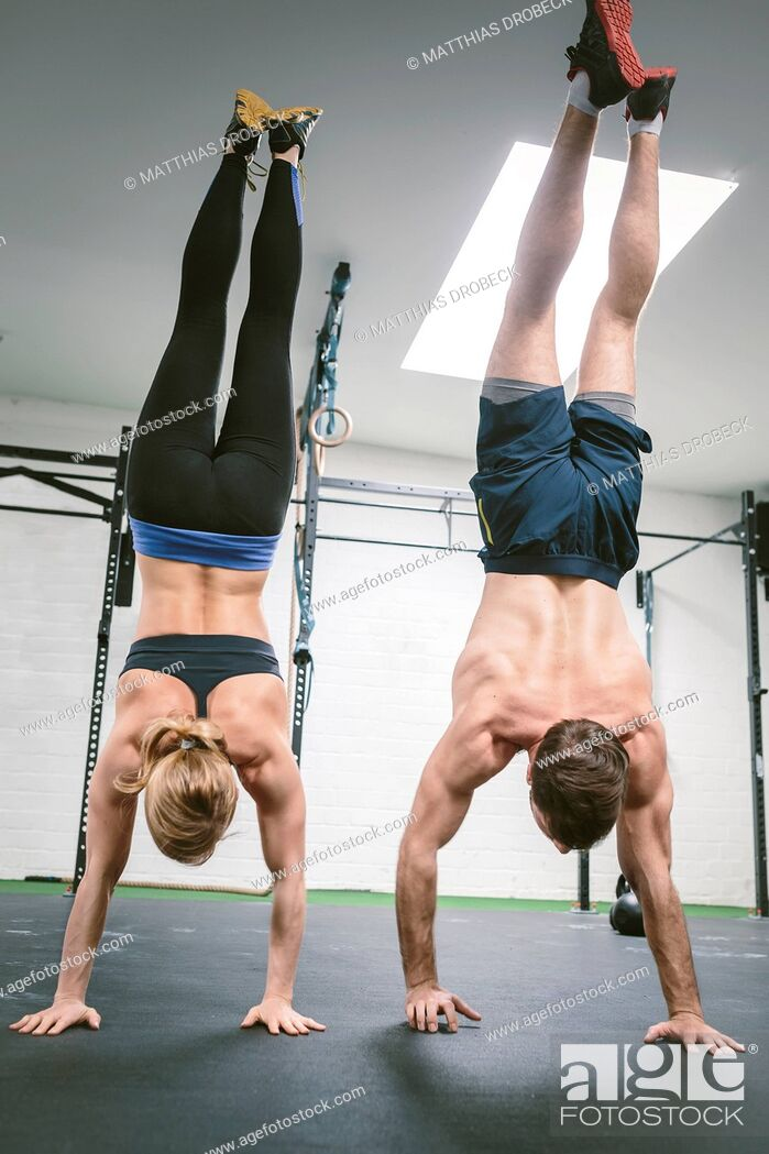 Stock Photo: Couple in gym training handstands.