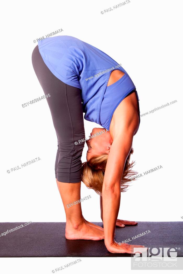 Stock Photo: Beautiful healthy woman doing Standing Forward Fold Uttanasana hamstring stretch yoga, on white.