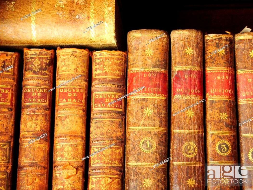 Stock Photo: Old books in a shelf in a private house. Old edition of Don Quijote.