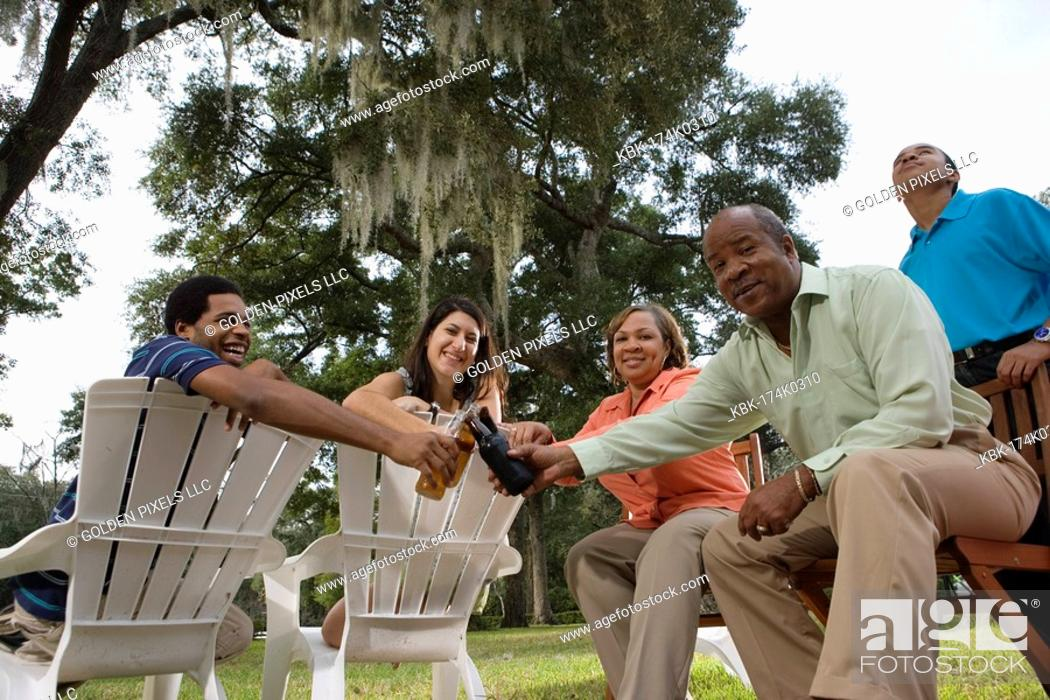 Imagen: Mature couple with their son toasting drinks with inter-racial couple while sitting on lawn chairs.
