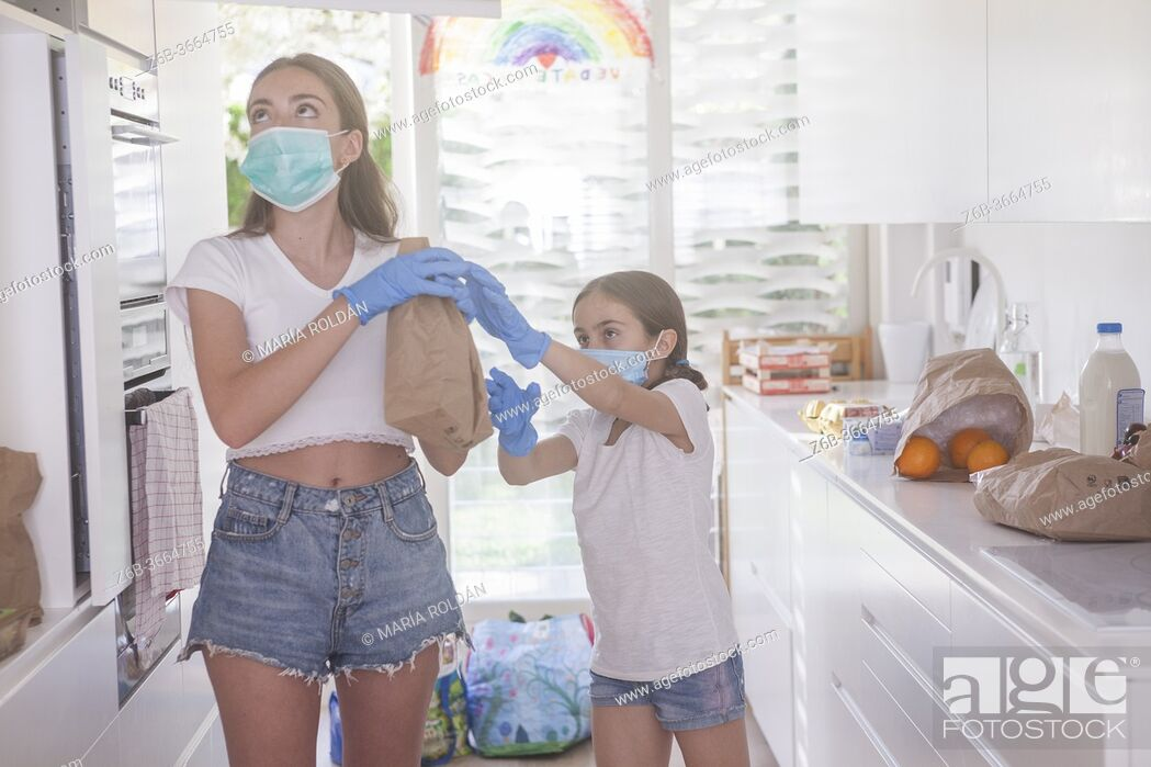 Stock Photo: kid helps her mom in the kitchen during pandemic.