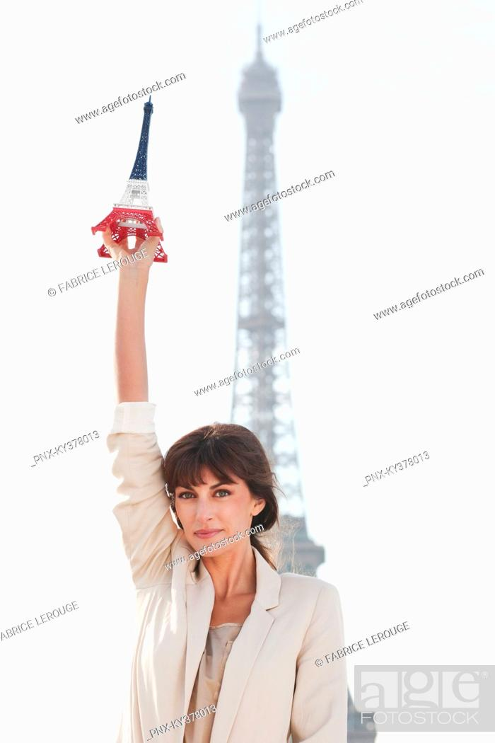 Stock Photo: Woman holding a replica of the Eiffel Tower in front of the original one, Paris, Ile-de-France, France.