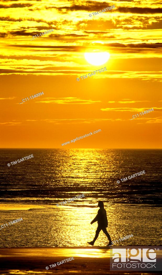 Stock Photo: one single man walking along beach at sunset with sea and sun behind.