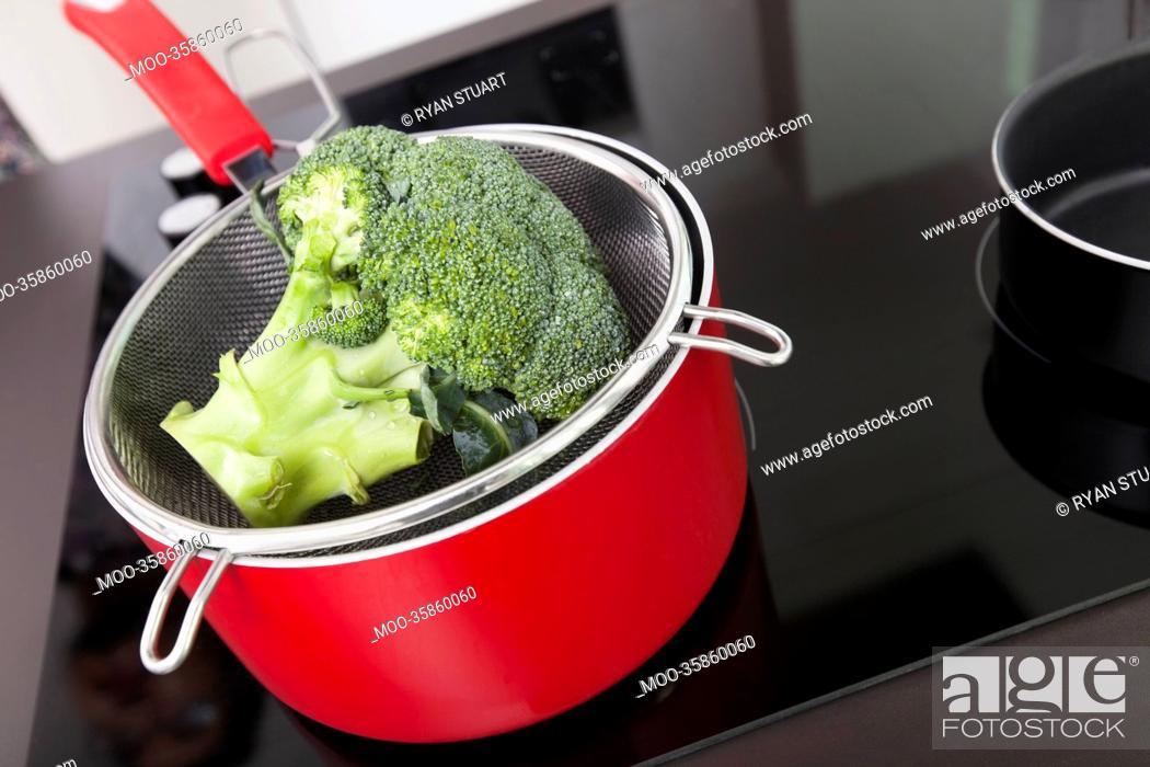 Stock Photo: Broccoli in saucepan on stove at kitchen.