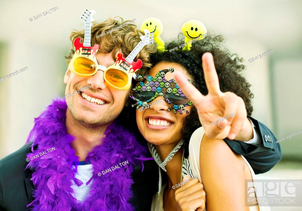 Imagen: Couple wearing decorative glasses at party.
