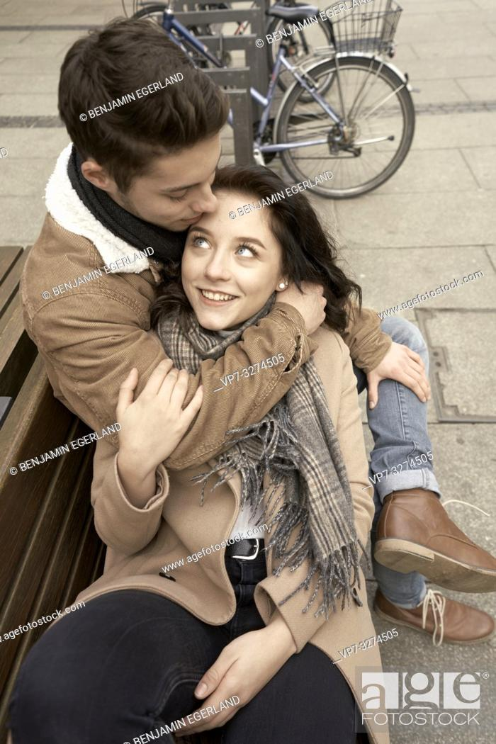 Stock Photo: young teenage woman laying in arm of boyfriend, affectionate couple relaxing together on bench in city, next to bicycles, in Cottbus, Brandenburg, Germany.