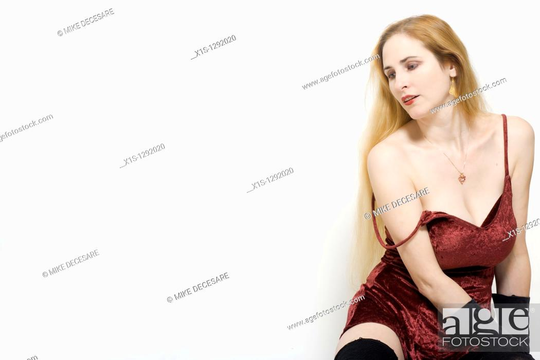 Stock Photo: Woman with long blond hair and fair skin sits on the floor wearing a short red dress with straps but one shoulder is exposed.