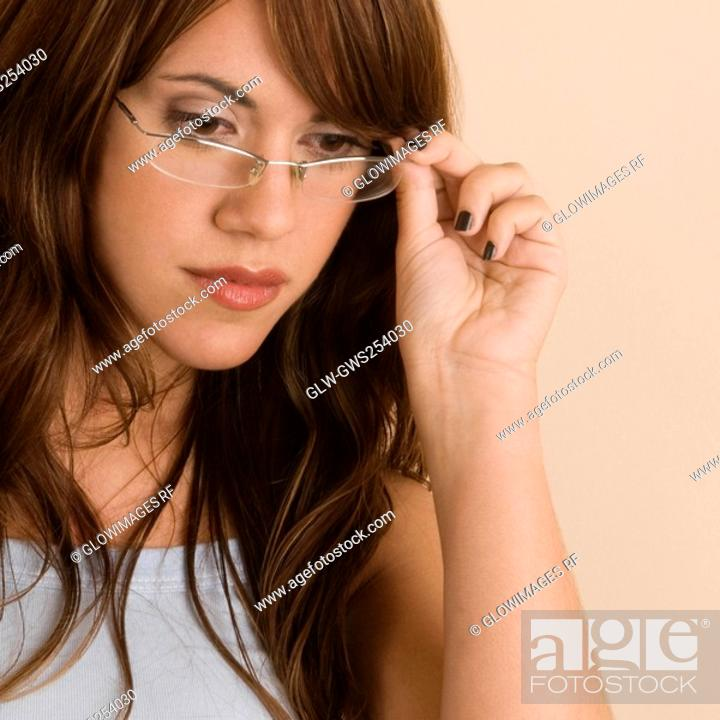 Stock Photo: Close-up of a young woman adjusting her eyeglasses.