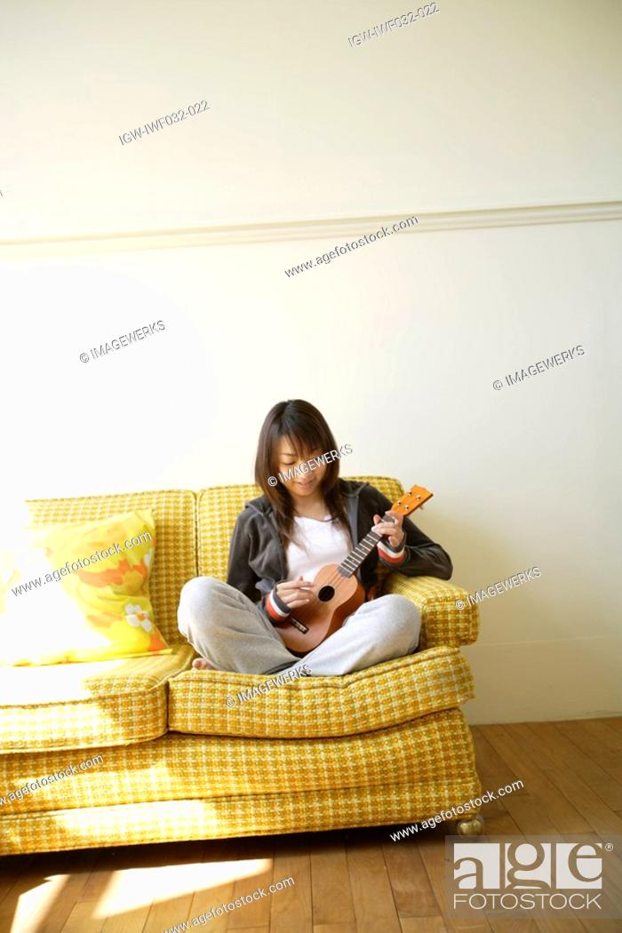 Stock Photo: View of a young woman playing guitar.