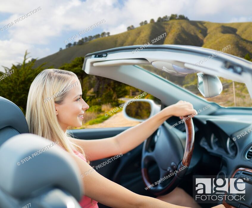 Stock Photo: happy young woman driving convertible car.