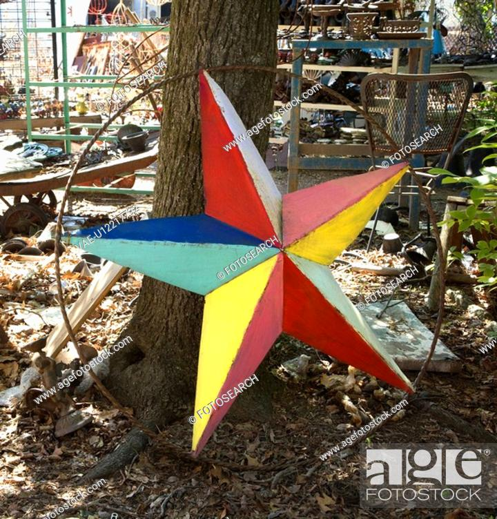 Stock Photo: Colorful painted star made of metal leaning against tree.