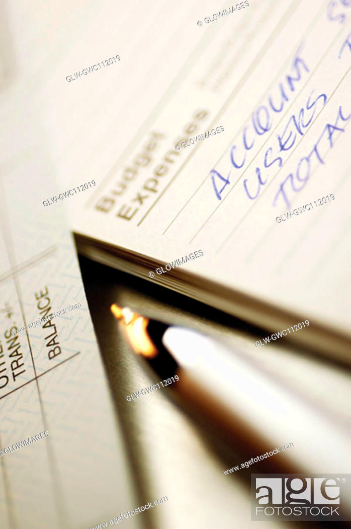 Stock Photo: Close-up of a pen with a bank deposit slip and a personal organizer.