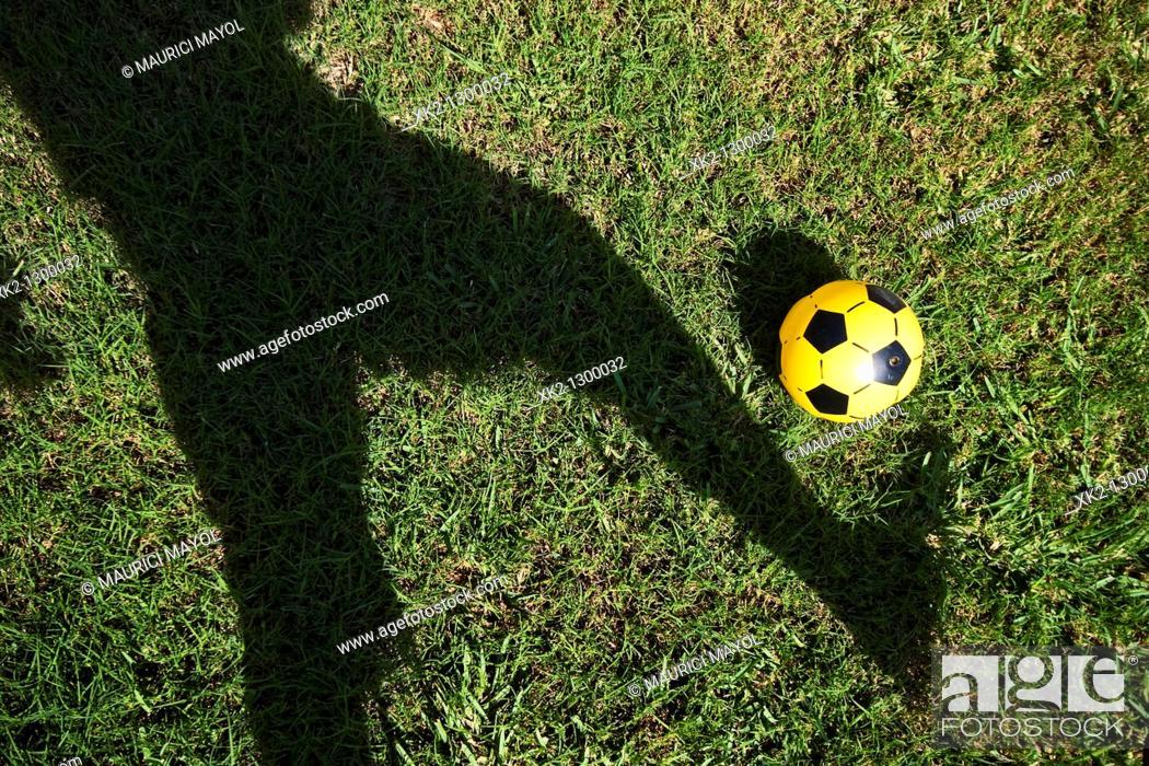 Stock Photo: sombra de jugador de futbol controlando un balón de plastico amarillo.