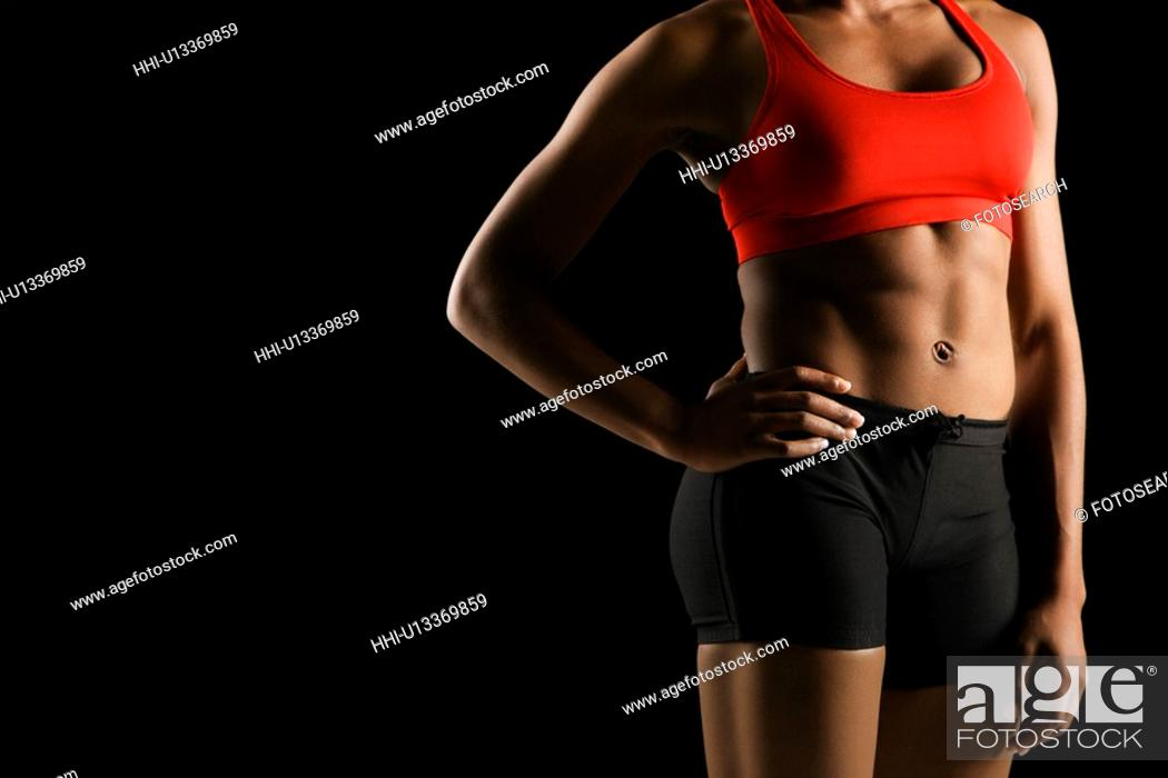 Stock Photo: Torso of muscular African American woman wearing athletic apparel with hand on hip.