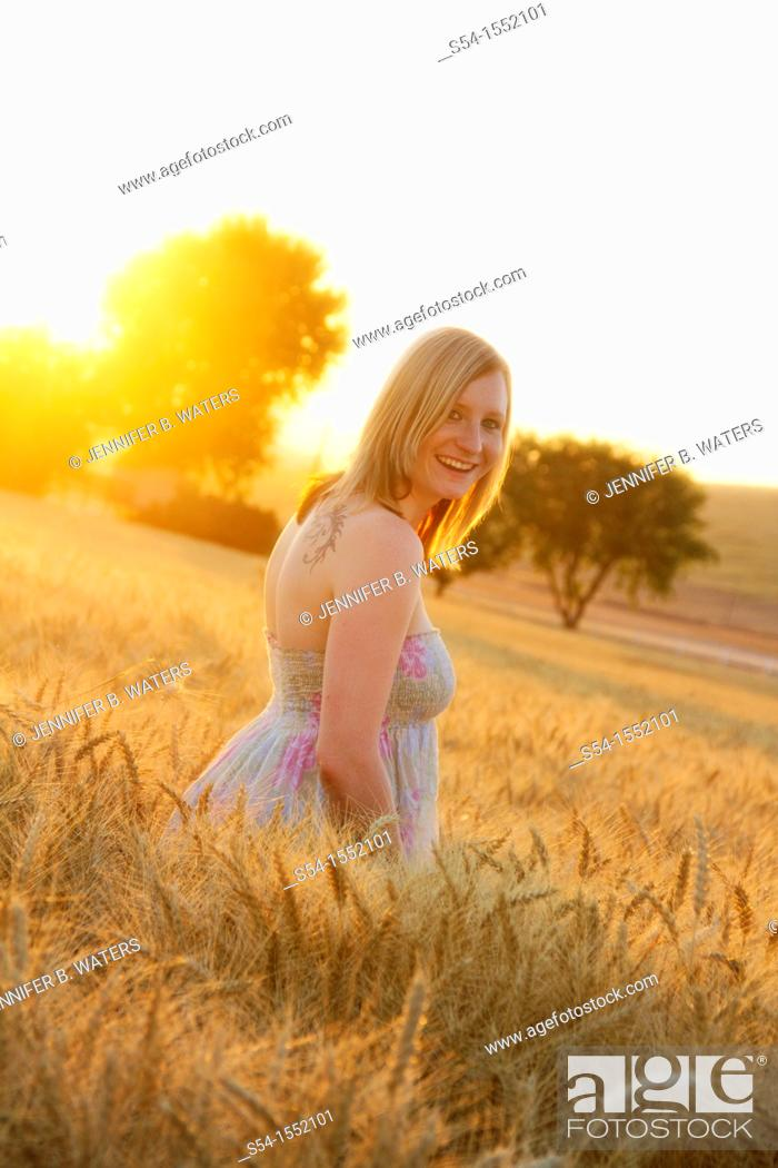 Stock Photo: A happy young woman in a field of barley in Lewiston, Idaho, USA.