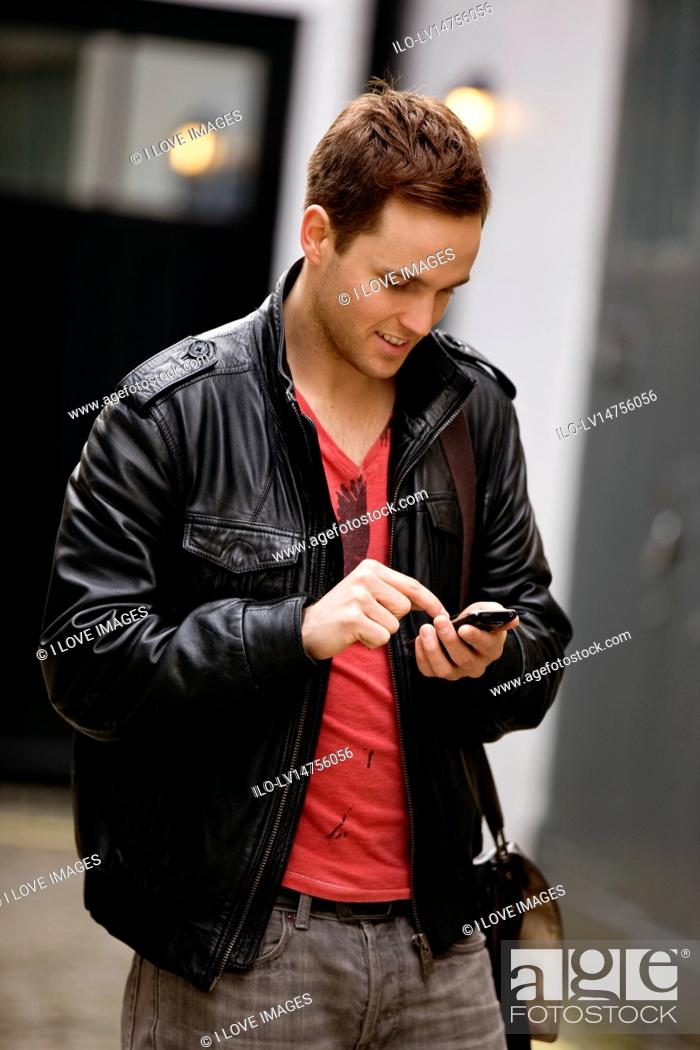 Stock Photo: A young man standing in the street, using his mobile phone.