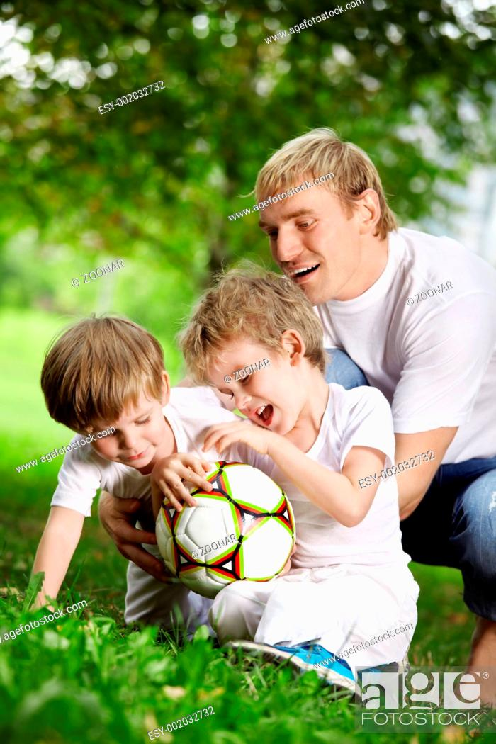 Stock Photo: Father and two sons play football in a summer garden.