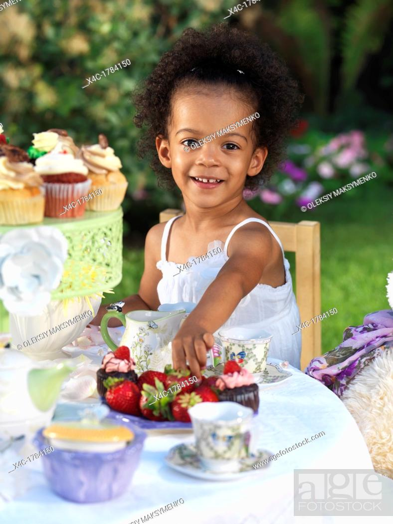 Stock Photo: Happy smiling three year old girl having a party outdoors.