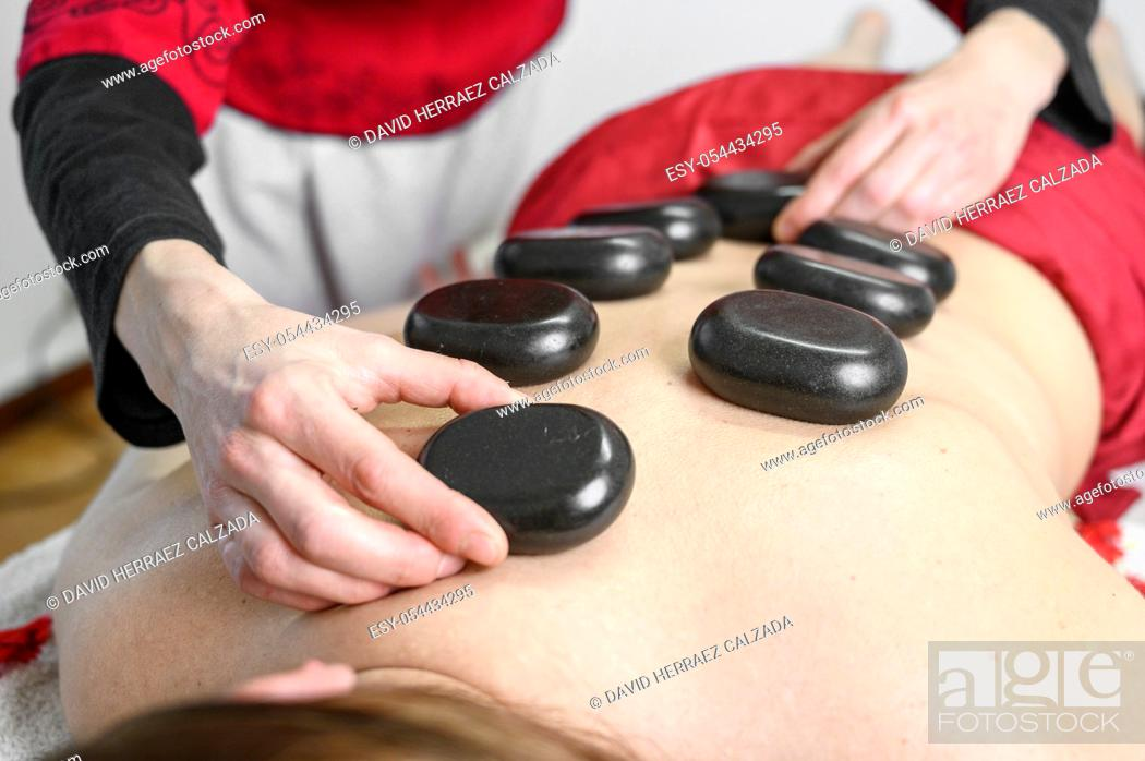 Stock Photo: Stone treatment. Young woman lying on front enjoying a massage at spa with hot stones on her back. Beauty treatment concept .