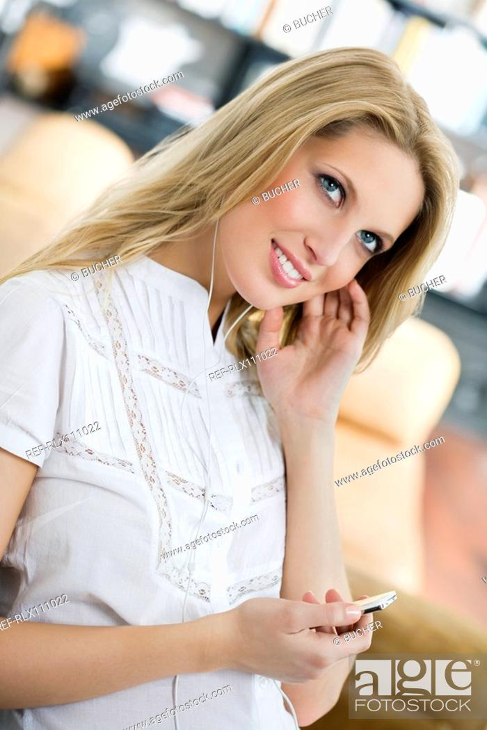 Stock Photo: Young woman listening to MP3 player.