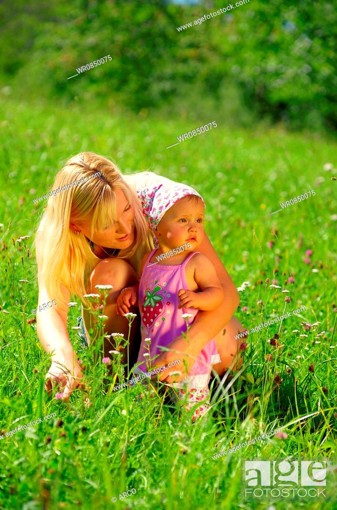 Stock Photo: Young mother with daughter in meadow.
