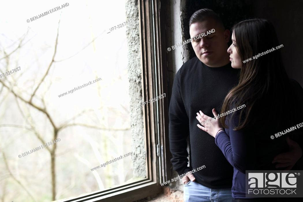 Stock Photo: sensitive woman touching emotional man, deep emotional bond, standing in dark shadow at window looking out at light, in Cottbus, Brandenburg, Germany.