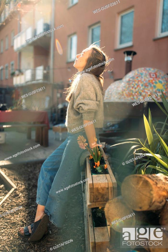Stock Photo: Young woman relaxing in garden in sunshine.