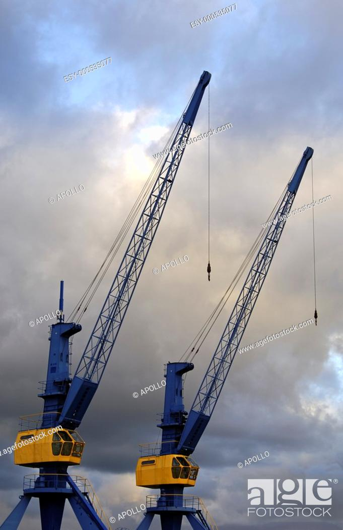 Stock Photo: Two inoperative cranes looming into a cloud-covered evening sky.