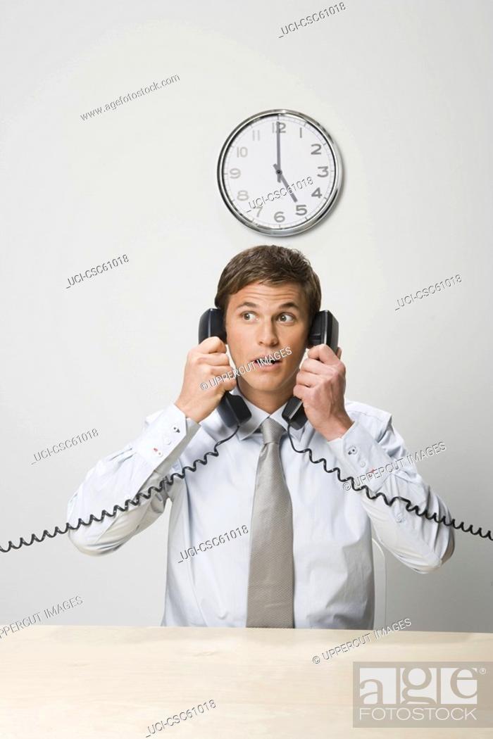 Stock Photo: Businessman talking on two telephones.