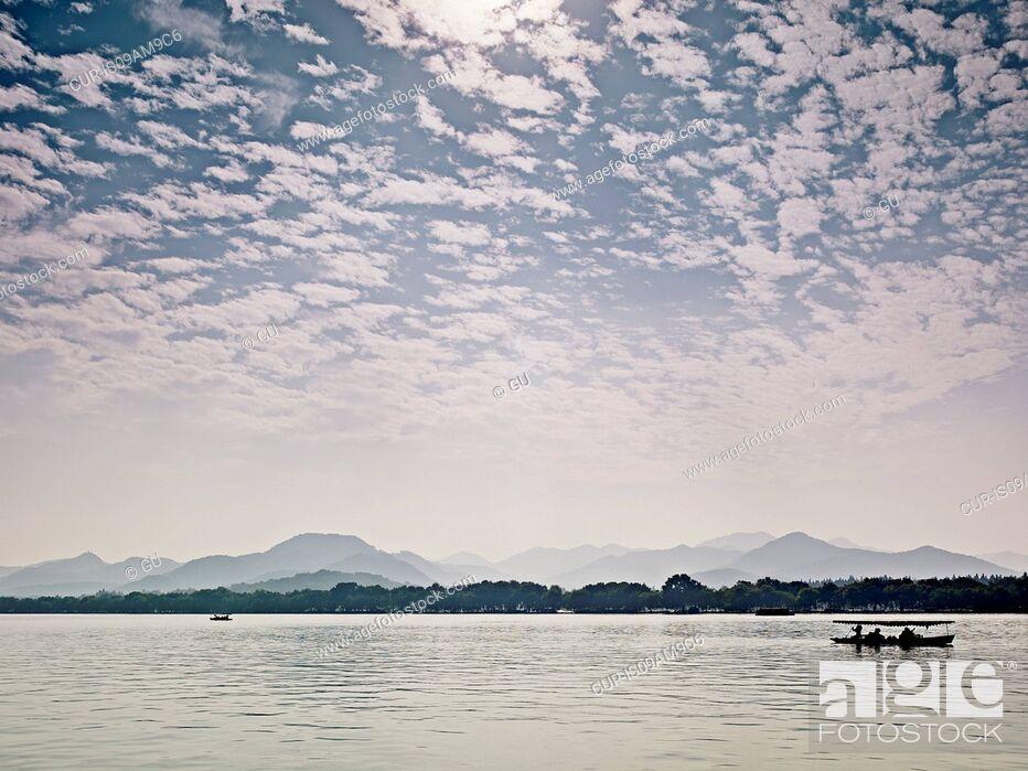 Imagen: Silhouetted fishing boat on West Lake, Hangzhou, Zhejiang, China.
