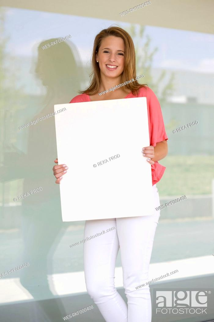 Stock Photo: Europe, Germany, North Rhine Westphalia, Duesseldorf, Young woman with placard, smiling, portrait.