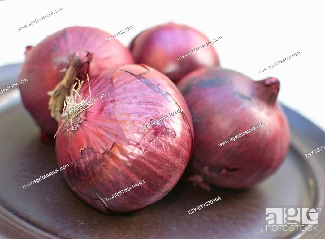 Stock Photo: Fresh red onions on dark plate isolated/outdoors from above.