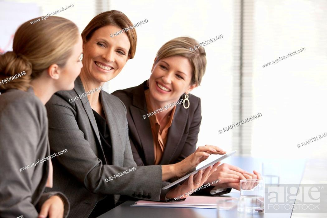 Stock Photo: Smiling businesswomen using digital tablet.