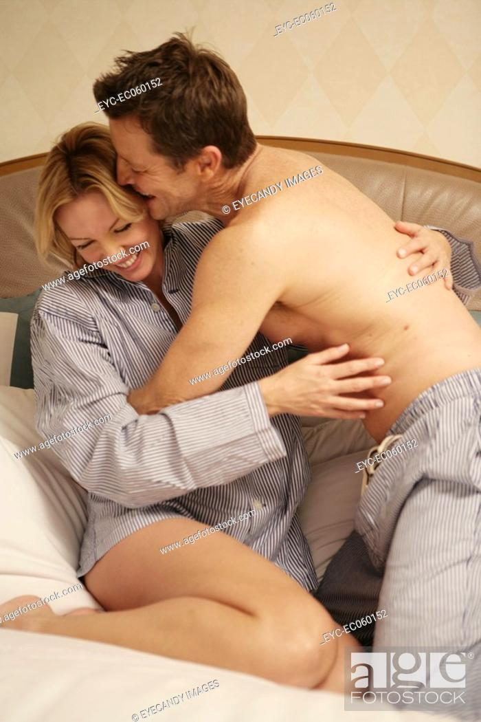 Stock Photo: Mature couple wrestling in bed.