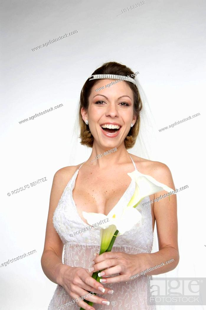 Stock Photo: Bride in her 20s smiles at the camera in a studio setting.