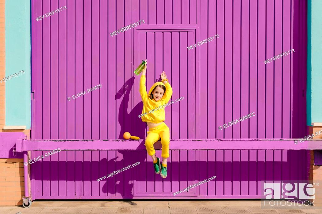 Stock Photo: Happy little girl dressed in yellow sitting on bar in front of purple garage door.