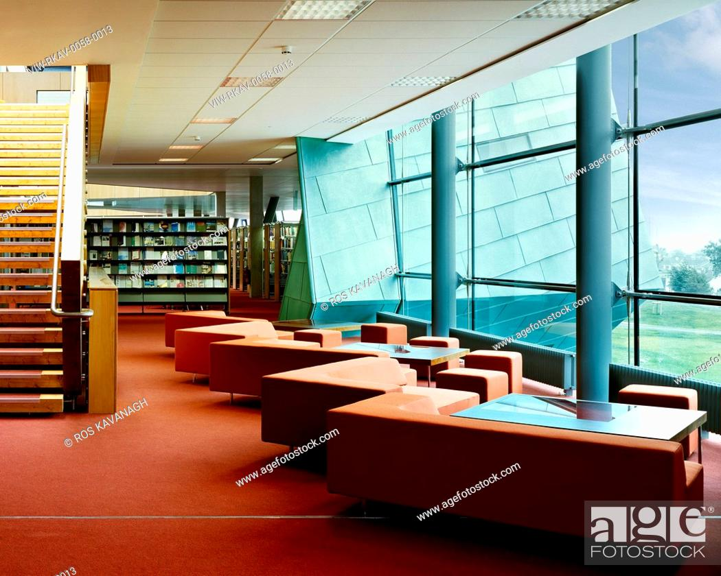 Stock Photo: Galway-Mayo Institute of Technology, Galway, Ireland. Architect: Murray O'Laoire, 2003. View of seating area in library showing stairs, shelving.