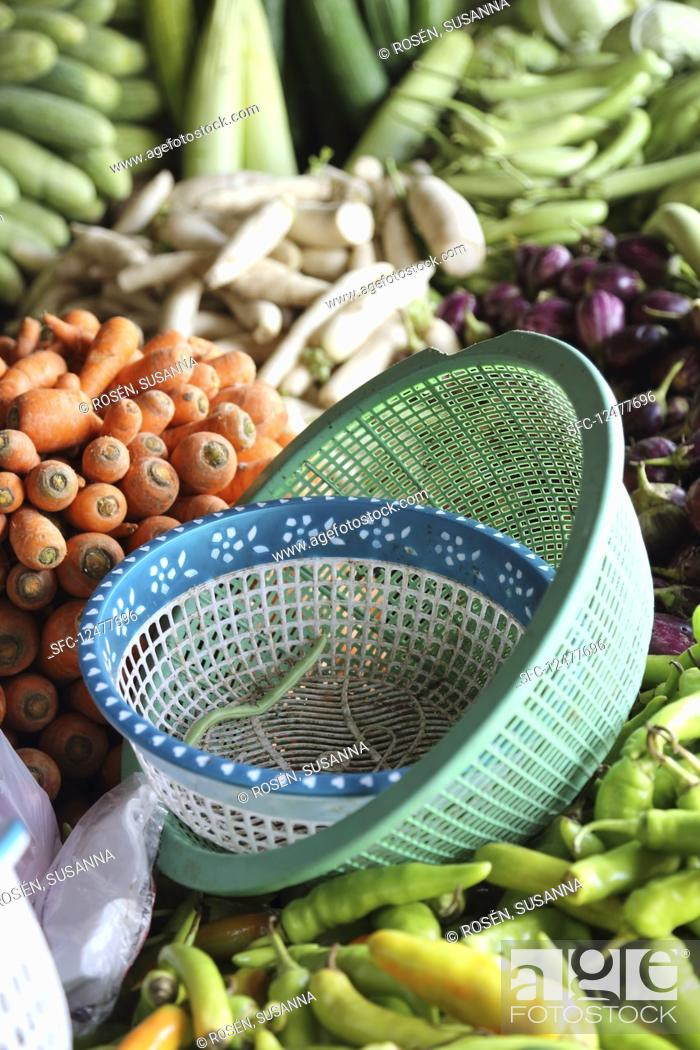 Stock Photo: A vegetable stand with plastic bowls in the foreground.