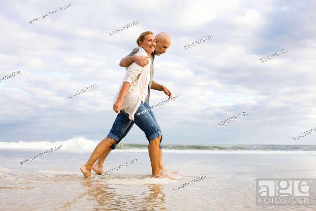 Stock Photo: Couple walking in the sea.