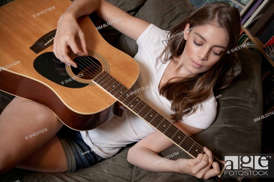 Stock Photo: Caucasian woman playing guitar on sofa.