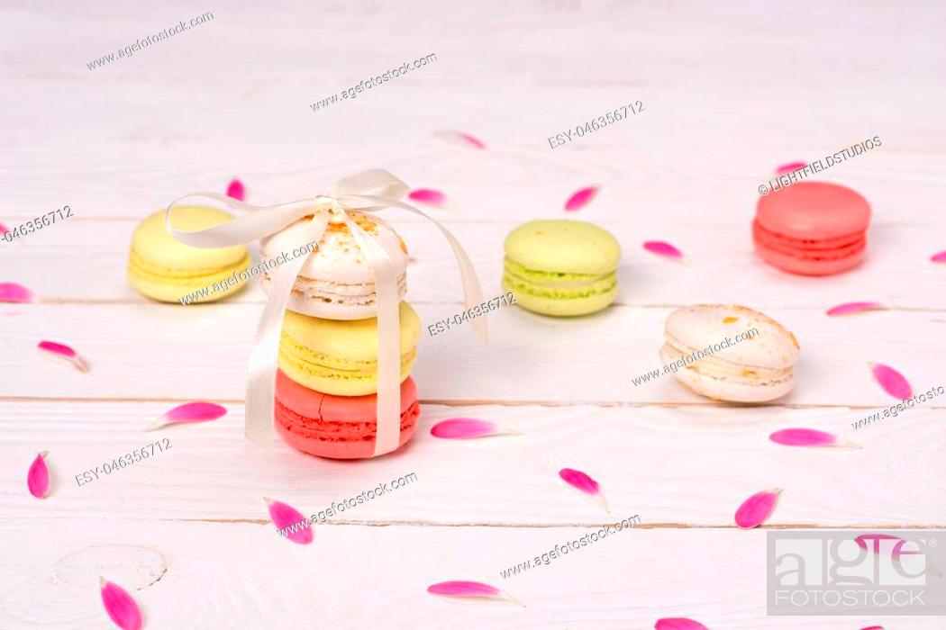 Stock Photo: Still life of fresh macarons on the table with pink petals. sweets background concept.