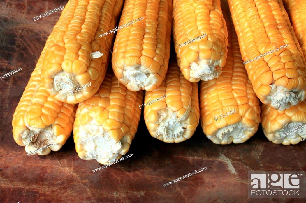 Stock Photo: ripe corn on brown background closeup.