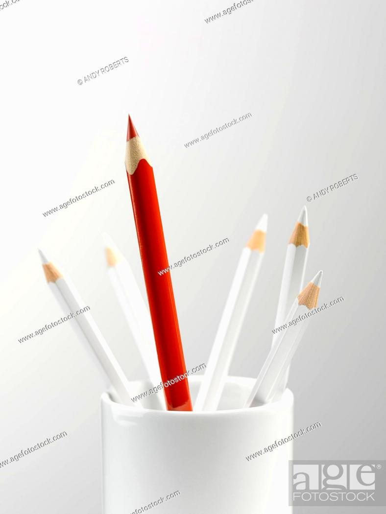 Stock Photo: Tall red pencil in cup with smaller white pencils still life.