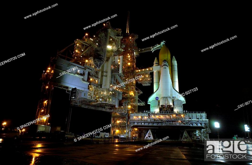 Stock Photo: 12/03/2001 -- Rain on the ground around Space Shuttle Endeavour on Launch Pad 39B reflects the many lights illluminating the Rotating Service Structure at left.