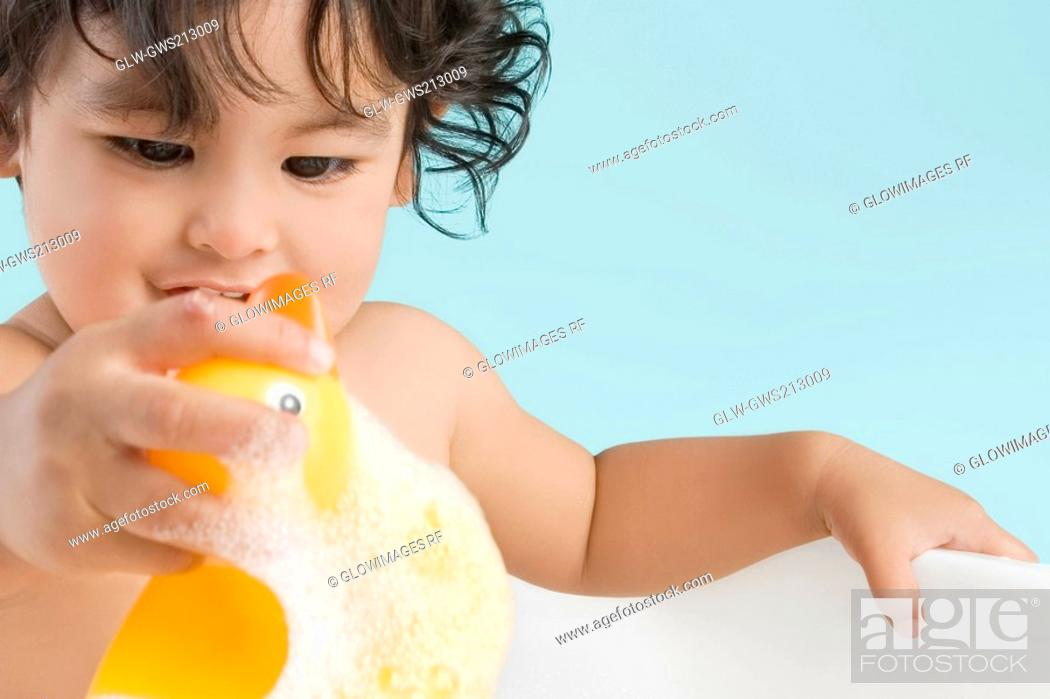 Stock Photo: Close-up of a boy sitting in a bathtub and smiling.